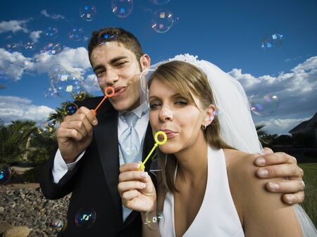 Close-Up Of Newlywed Couple Blowing Bubbles With A Bubble Wand