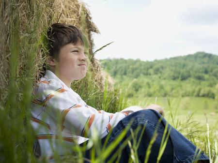 Portrait Of A Boy Sitting Against A Hay Bale
