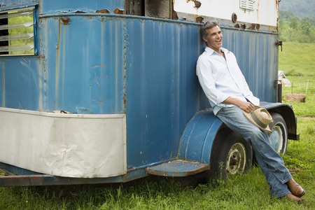 Man Leaning Against A Horse Trailer