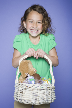 Portrait Of A Girl Holding Easter Bunnies And Easter Eggs In A Wicker Basket LANG_EVOIMAGES