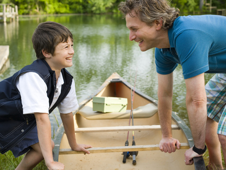 Portrait Of A Man And His Son Bending Forward Over A Canoe