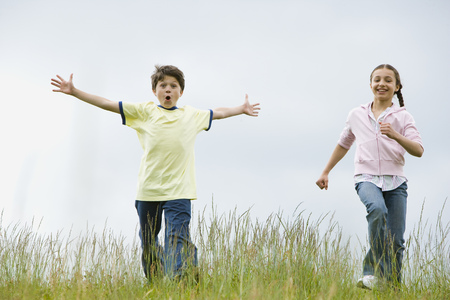 Boy And A Girl Running In A Field