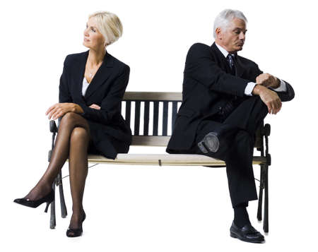 Businessman And Businesswoman Sitting On A Bench