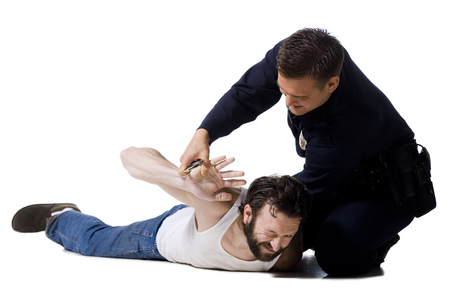 Police Officer Arresting Man Lying Down With Handcuffs