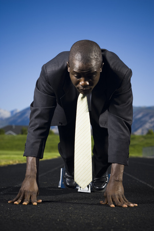 Businessman In Starting Position Ready To Race LANG_EVOIMAGES