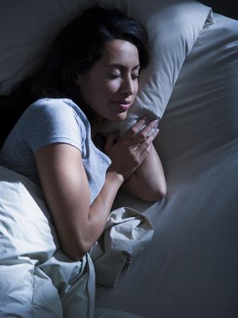 Mujer en la cama en la oscuridad