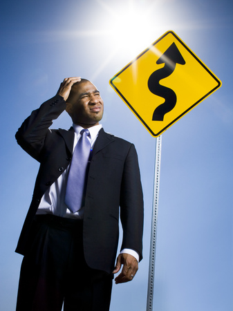 Confused Businessman In Front Of Road Sign LANG_EVOIMAGES