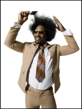 Man With An Afro In Beige Suit Combing With A Hair Pick LANG_EVOIMAGES
