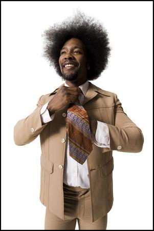 Man With An Afro In Beige Suit Adjusting Necktie