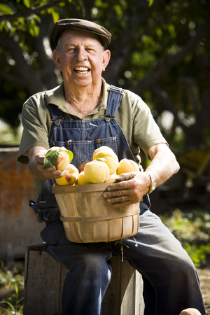 Farmer Posing With A Basket Of Peaches