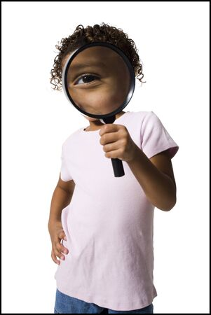 finding out: Young Girl Looking Through Magnifying Glass LANG_EVOIMAGES