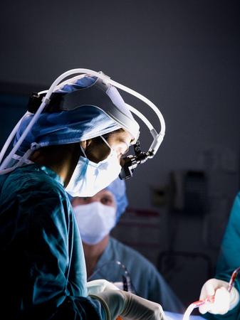caregivers: Female Doctor In Scrubs With Head Light In Surgery LANG_EVOIMAGES
