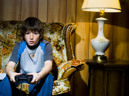 Boy With Video Game Controller On Sofa LANG_EVOIMAGES