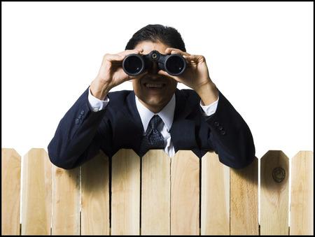 Businessman Looking Through Binoculars Over Wooden Fence