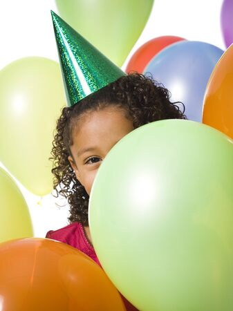 Young Girl Wearing Party Hat And Playing Amongst Balloons