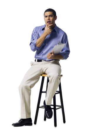 front facing: Man Sitting On Stool With Clipboard Gesturing LANG_EVOIMAGES