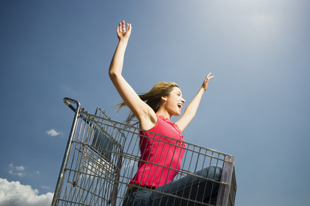 Woman In Shopping Cart Outdoors With Arms Up Smiling
