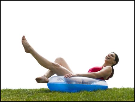 Woman In Bikini Lying In Swimming Ring On Grass Smiling
