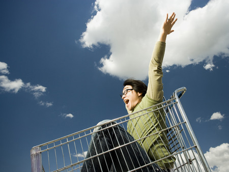 Man With Eyeglasses In Shopping Cart Outdoors With Arms Up Smiling