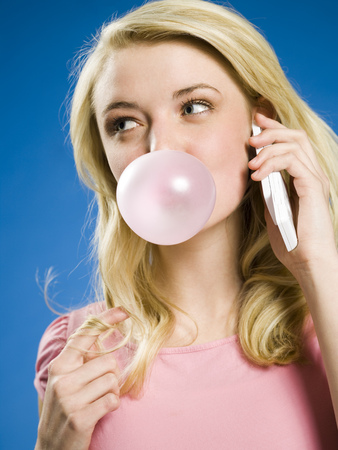 Girl Talking On Cell Phone And Blowing Bubble LANG_EVOIMAGES