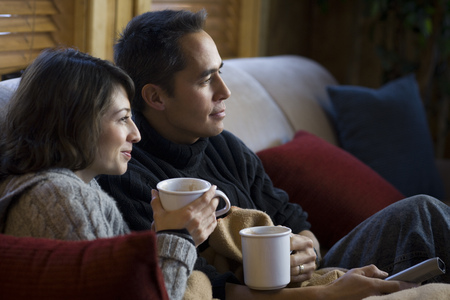 Man And Woman On Sofa With Mugs And Remote LANG_EVOIMAGES