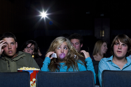 provoking: Girl Talking On Cell Phone At Movie Theater With Annoyed Boy LANG_EVOIMAGES