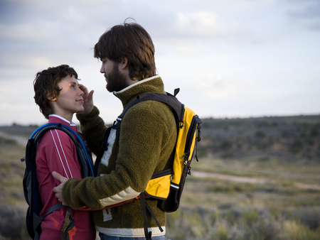 Man And Woman With Backpacks Embracing Outdoors
