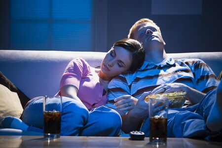 Couple Asleep On Sofa With Bowl Of Popcorn