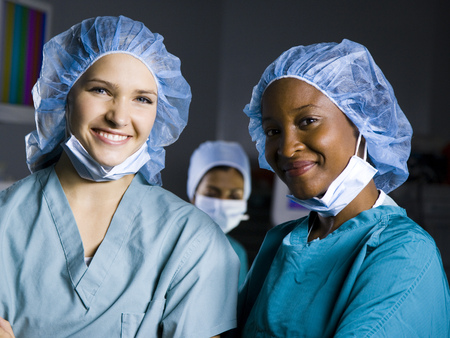 Female Surgeon And Nurse In Scrubs Smiling LANG_EVOIMAGES