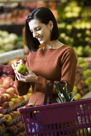 Woman Holding Green Apples At Grocery Store With Shopping Basket LANG_EVOIMAGES