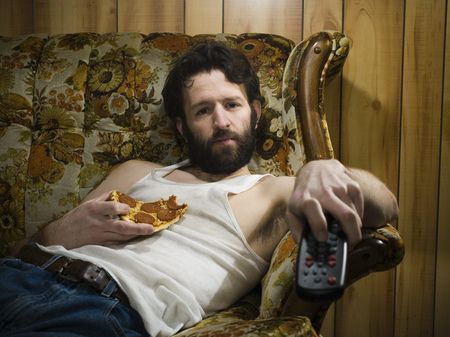Man On Sofa With Pizza And Remote LANG_EVOIMAGES