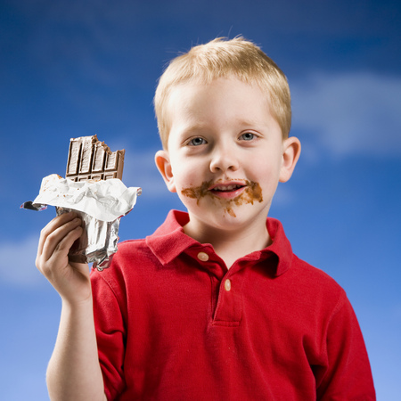 Boy Eating Chocolate Bar With Blue Sky LANG_EVOIMAGES