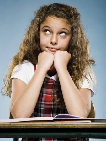 Girl Sitting At Desk With Workbook Looking Bored