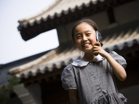 Girl Standing Outdoors With Cell Phone In Front Of Pagoda Smiling