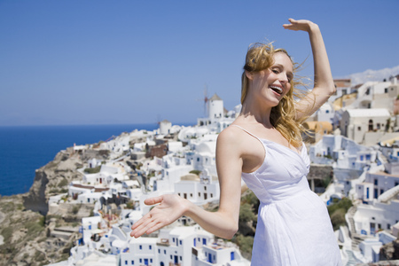 Woman Smiling With Arms Up And Village In Background