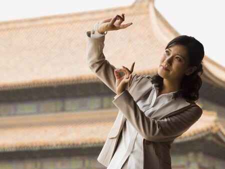 Businesswoman Doing Tai Chi Outdoors Smiling