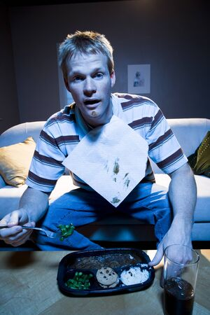 Man On Sofa With Frozen Dinner And Napkin With Food LANG_EVOIMAGES