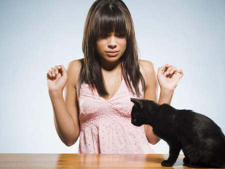 cowering: Scared Woman With Black Kitten LANG_EVOIMAGES