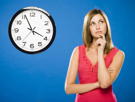 Woman With Arms Crossed Looking At Wall Clock Attached To Plumbing Pipes LANG_EVOIMAGES