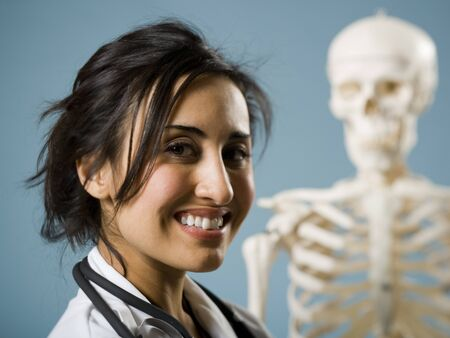 caregivers: Female Doctor Smiling With Skeleton In Background LANG_EVOIMAGES