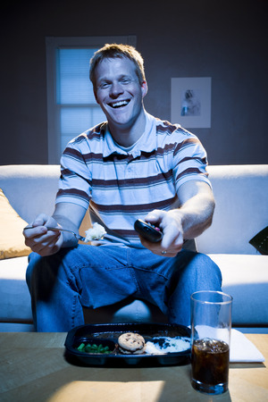Man On Sofa With Frozen Dinner And Napkin With Food Smiling LANG_EVOIMAGES