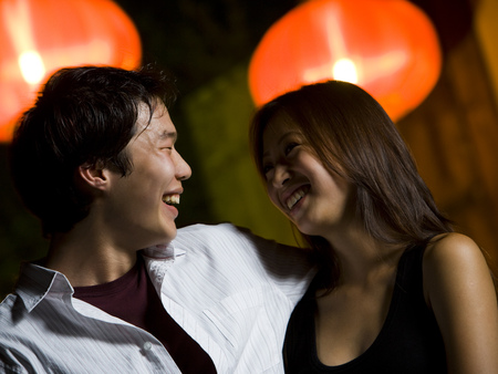 Couple Embracing Outdoors At Night Smiling
