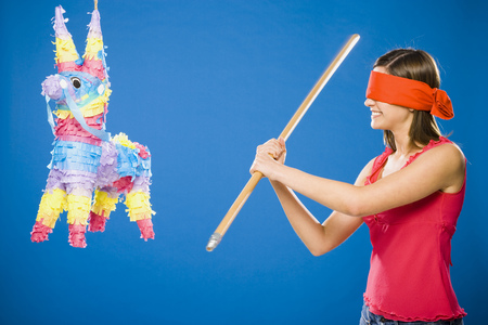 Woman With Blindfold Hitting Pinata With Stick