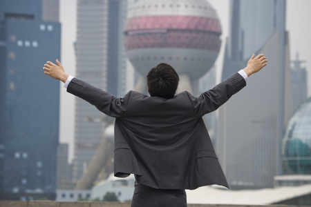 Rear View Of Businessman With Arms Up Facing City Skyline