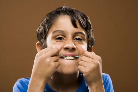 Closeup Of Boy Flossing Teeth