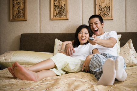 Couple In Bed Snuggling And Watching Television LANG_EVOIMAGES