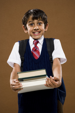 Boy With Backpack Holding Textbooks Smiling