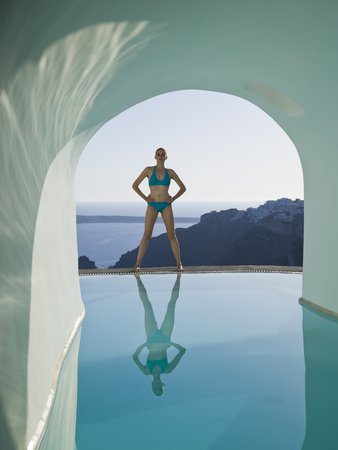 Woman In Bikini Standing At Edge Of Infinity Pool Outdoors With Arch And Rock Formation LANG_EVOIMAGES