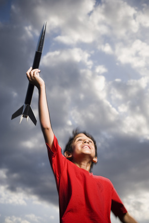 Boy Playing With Toy Rocket Outdoors On Cloudy Day Low Angle View