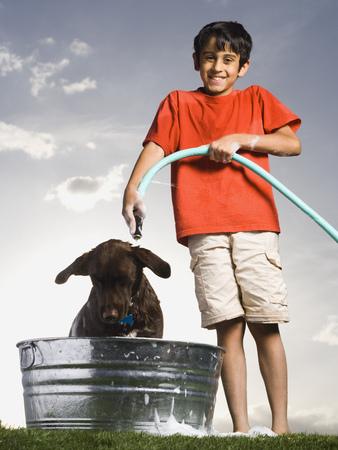 adentro y afuera: Niño bañando perro al aire libre en día nublado sonriendo